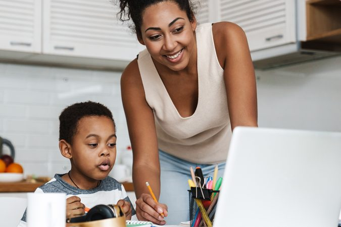 Black mother using laptop while doing homework with her son at home